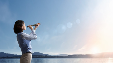 Photo pour Young businesswoman looking in spyglass on sunrise at horizon - image libre de droit
