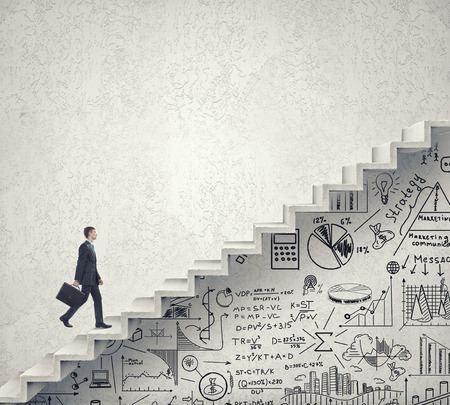 Foto de Businessman climbing up staircase as symbol of career rise - Imagen libre de derechos