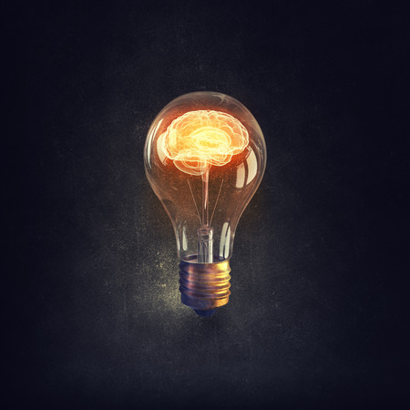 Foto de Human brain glowing inside of light bulb on dark background - Imagen libre de derechos