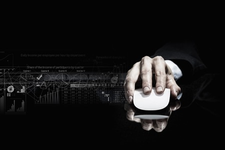 Photo pour Hand of businessman in suit on dark background using wireless computer mouse - image libre de droit