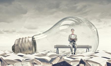 Photo pour Young businessman inside of light bulb reading book - image libre de droit
