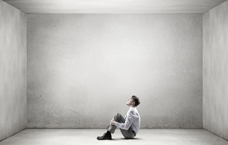 Foto de Young depressed businessman sitting on floor alone in empty room - Imagen libre de derechos