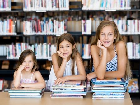 Photo pour Little girls reading books in library - image libre de droit