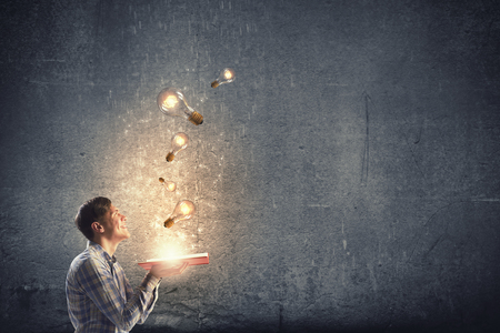 Foto de Young man holding opened book with glass glowing light bulbs flying out - Imagen libre de derechos