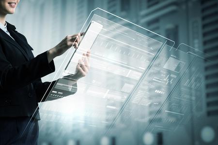 Photo pour Businesswoman with tablet pc against high tech background - image libre de droit