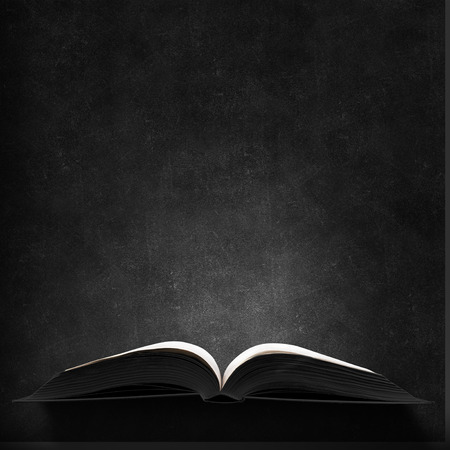 Photo for Opened book with light on pages on black background - Royalty Free Image