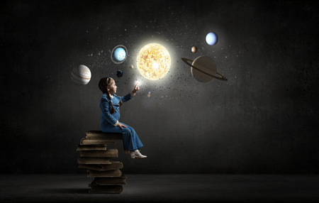 Photo pour Little girl sitting on stack of books and touching planet - image libre de droit