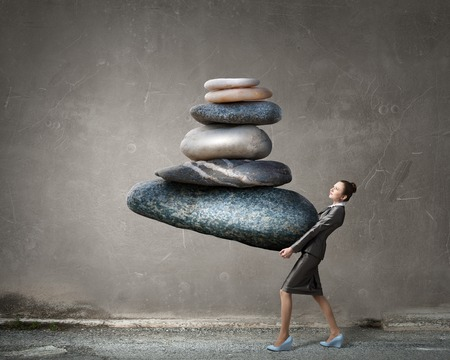 Foto de Attractive businesswoman carrying stack of stones in hands - Imagen libre de derechos