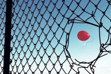 Photo pour Red balloon flying in clear sky seen in hole of fence - image libre de droit