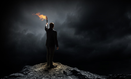 Photo for Young businessman in darkness holding burning torch in hand - Royalty Free Image