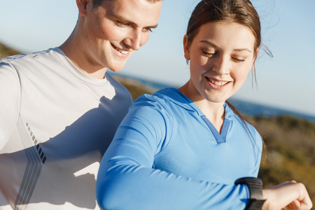 Foto per Runner woman with heart rate monitor running on beach - Immagine Royalty Free