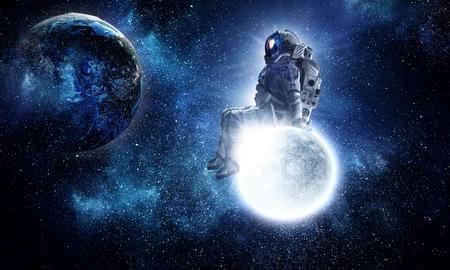 Foto de Astronaut sit on full moon. Mixed media - Imagen libre de derechos