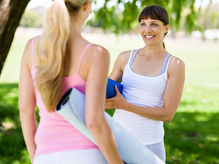 Photo for Two young women with a gym mat chatting in the park - Royalty Free Image