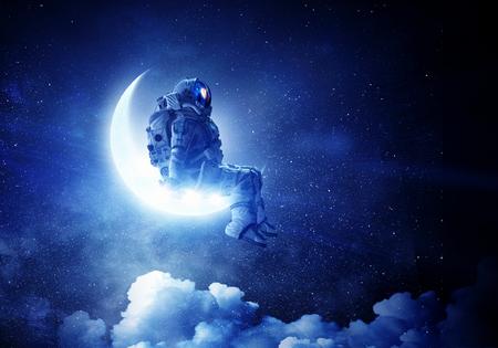 Foto de Spaceman sitting on moon against dark starry sky. Mixed media - Imagen libre de derechos