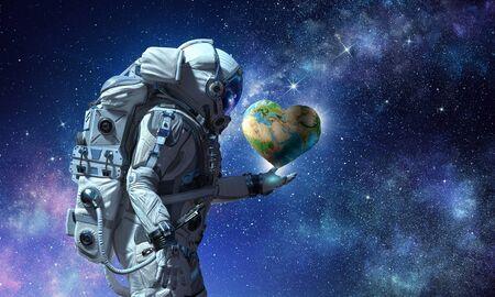 Photo pour Astronaut holding Earth planet in palm. - image libre de droit