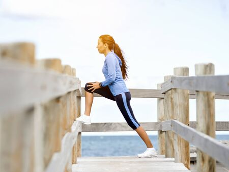 Photo for Young woman at the beach doing exercises - Royalty Free Image
