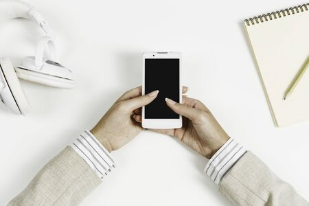 Photo pour Top view of businesswoman hand with smartphone over white table - image libre de droit