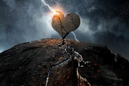 Photo for Broken heart of stone on rock top. Mixed media - Royalty Free Image
