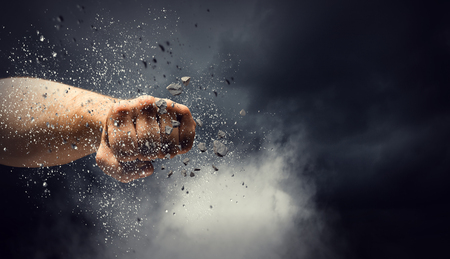 Foto de Male hand breaking with fist concrete wall. Mixed media - Imagen libre de derechos