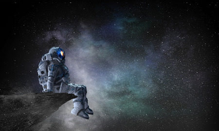 Photo for Astronaut sitting on cliff edge against dark starry sky. Mixed media - Royalty Free Image