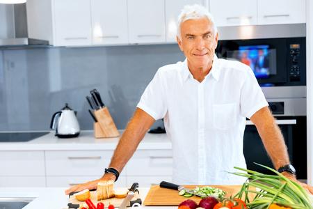 Photo pour Portrait of a smart senior man standing in kitchen - image libre de droit