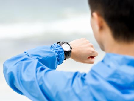 Foto de Young man in sportswear using smartwatch - Imagen libre de derechos