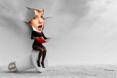 Photo for Excited worried woman with face over a torn hole of paper sitting on a lamp - Royalty Free Image