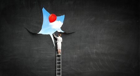 Foto de Businesswoman on ladder and torn wallpaper on wall. Mixed media - Imagen libre de derechos