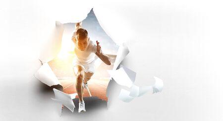 Foto de Atlete man running through torn wallpaper on wall. Mixed media - Imagen libre de derechos