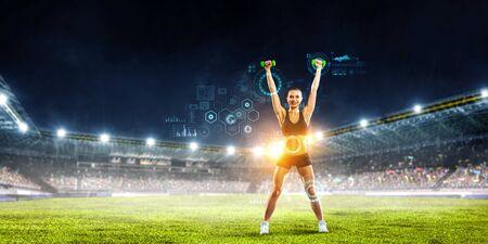 Foto de Sporty woman with dumbbells in hands and graphs on screen. Mixed media - Imagen libre de derechos