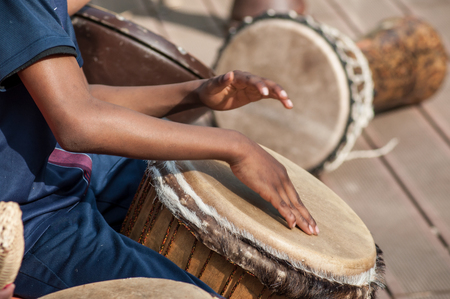 Photo for Closeup of kid's hands on African drums in outdoor - Royalty Free Image