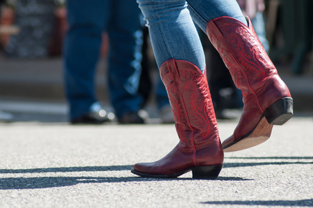 Photo pour closeup of woman legs with red american boots at country show in outdoor  - image libre de droit