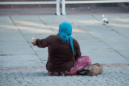 Foto de Strasbourg - France - 20 April 2019 -  poor woman  with plastic cup in hands sitting in the street - Imagen libre de derechos