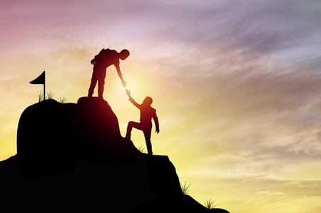 Foto de silhouette people helping hand to climb mountain rock, concept as winner, improvement and goal to success in business and sport - Imagen libre de derechos