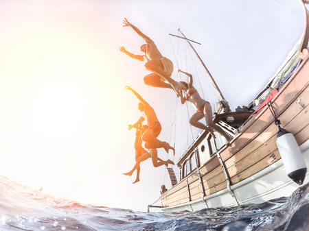 Photo pour Multiracial young people diving from sailing boat into the sea - Cheerful friends having fun in summer party day - Vacation and friendship concept - Soft focus on right man - Fisheye lens distortion - image libre de droit