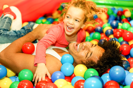 Photo for Young father playing with his daughter inside ball pit swimming pool - Happy people having fun in children playground indoor - Family and love concept - Soft focus on man face - Warm vivid filter - Royalty Free Image