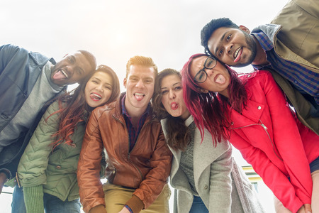 Photo for Happy friends taking selfie photo making funny faces with back sun light - Young multiracial people having fun together outdoor - Multi race friendship concept - Focus on two right guys - Warm filter - Royalty Free Image