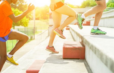Foto de Runners training in stadium on terrace stairs with back sun light - Young athletes preparing for college competition - Healthy lifestyle and sport concept - Focus on center shoes - Warm filter - Imagen libre de derechos