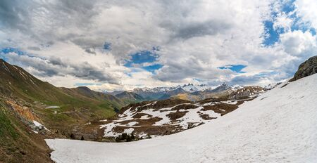 Photo pour Panorama of alpine valley and mountains in spring with large snowfield in the foreground and a mountain road on the left - image libre de droit