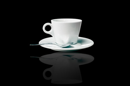 white coffee cup and saucer with spoon over black background