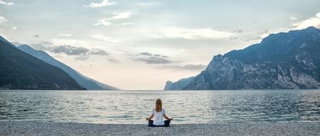 Photo pour Woman meditating at the lake - image libre de droit