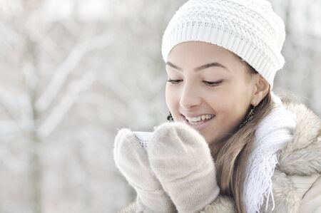 Head high key portrait of beautiful happy young woman smiling, holding cup of hot drink, outdoor, winter