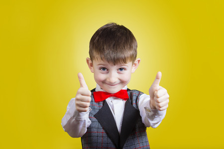 Photo for Excited Surprised  little boy with thumb up gesture isolated over yellow background. - Royalty Free Image