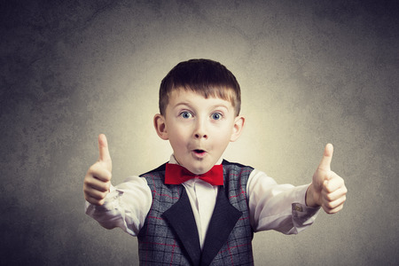 Photo pour Excited Surprised little boy with thumb up gesture isolated over grey background. - image libre de droit