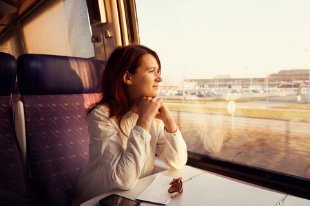 Young woman traveling looking out the window while sitting in the train.