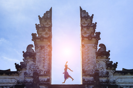 Photo for Woman traveler jumping with energy and vitality in the gate of a temple, Bali, Indonesia - Royalty Free Image