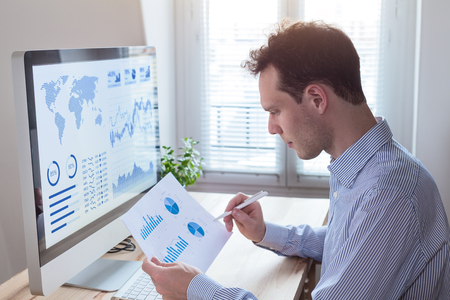 Foto de Investor analyzing financial reports and key performance indicators (KPI) of stock market on the computer screen with business intelligence (BI) analytics and graphs at the office - Imagen libre de derechos