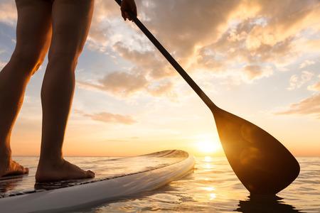 Foto de Stand up paddle boarding on a quiet sea with warm summer sunset colors, close-up of legs - Imagen libre de derechos