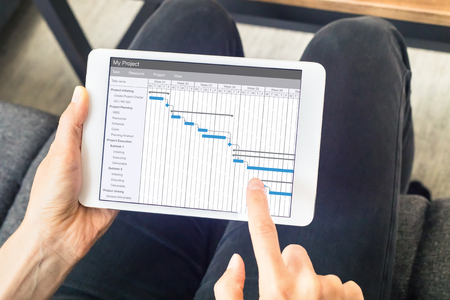 Foto de Project manager working with Gantt chart with planning software on digital tablet computer to update the schedule and deadlines - Imagen libre de derechos
