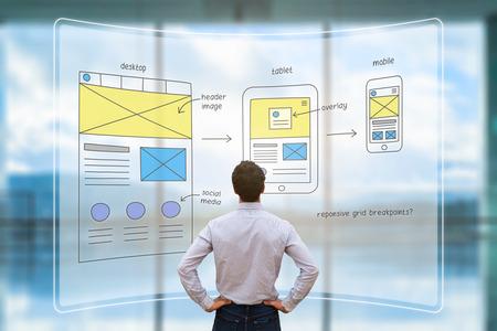 Foto de Website development UI/UX front end designer reviewing sketched wireframe layout design mockup for responsive web content with AR screen - Imagen libre de derechos